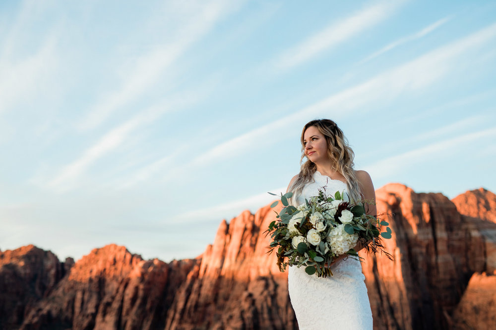 Bride holds bouquet sunrise elopement in Snow Canyon State Park Utah