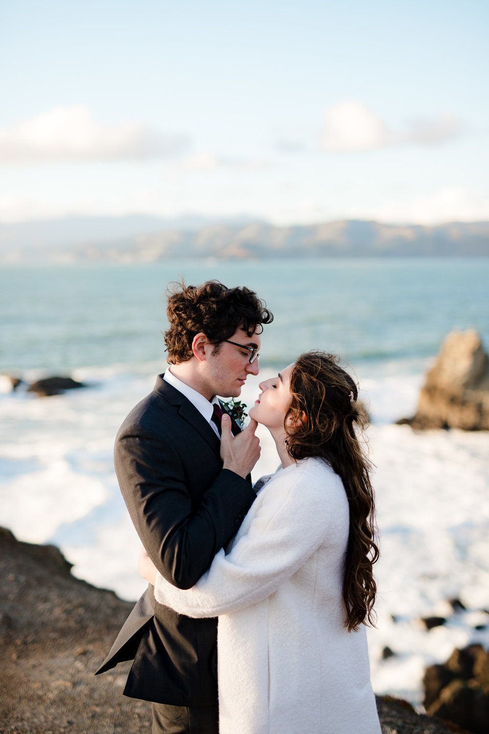 Intimate portrait of bride and groom standing on the shore near San Francisco elopement