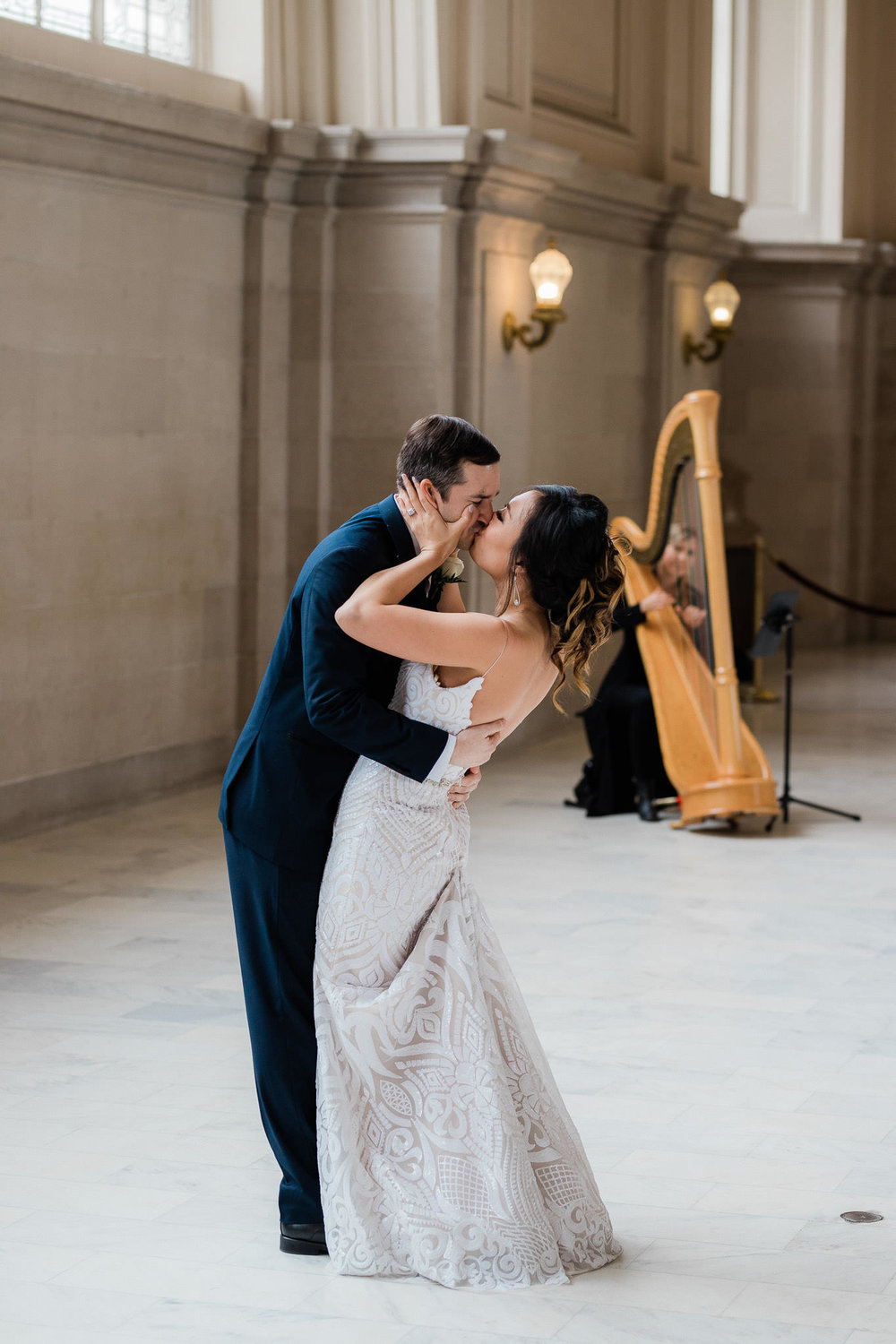 Bride and groom kiss after dancing to professional harp music during their San Francisco City Hall elopement