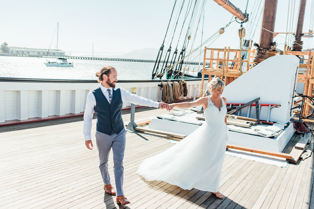 Bride and groom laugh and walk together on the deck of a historical ship in San Francisco