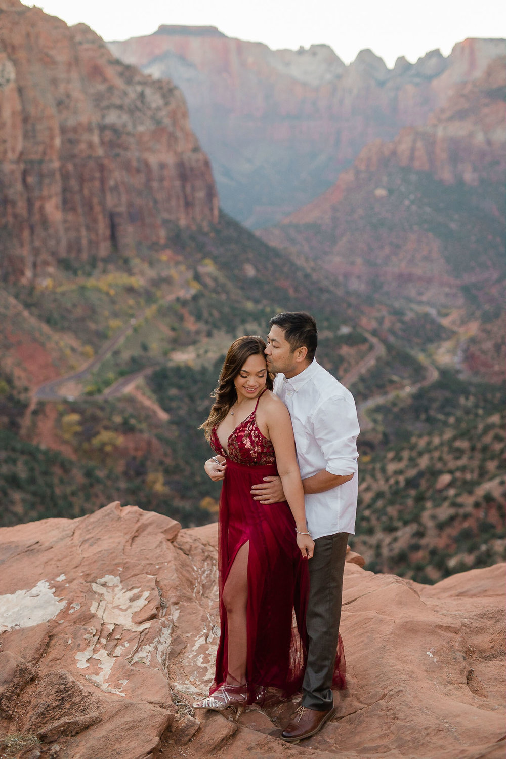 Guy holds girl and kisses her forehead at Canyon Overlook for their Zion National Park engagement session