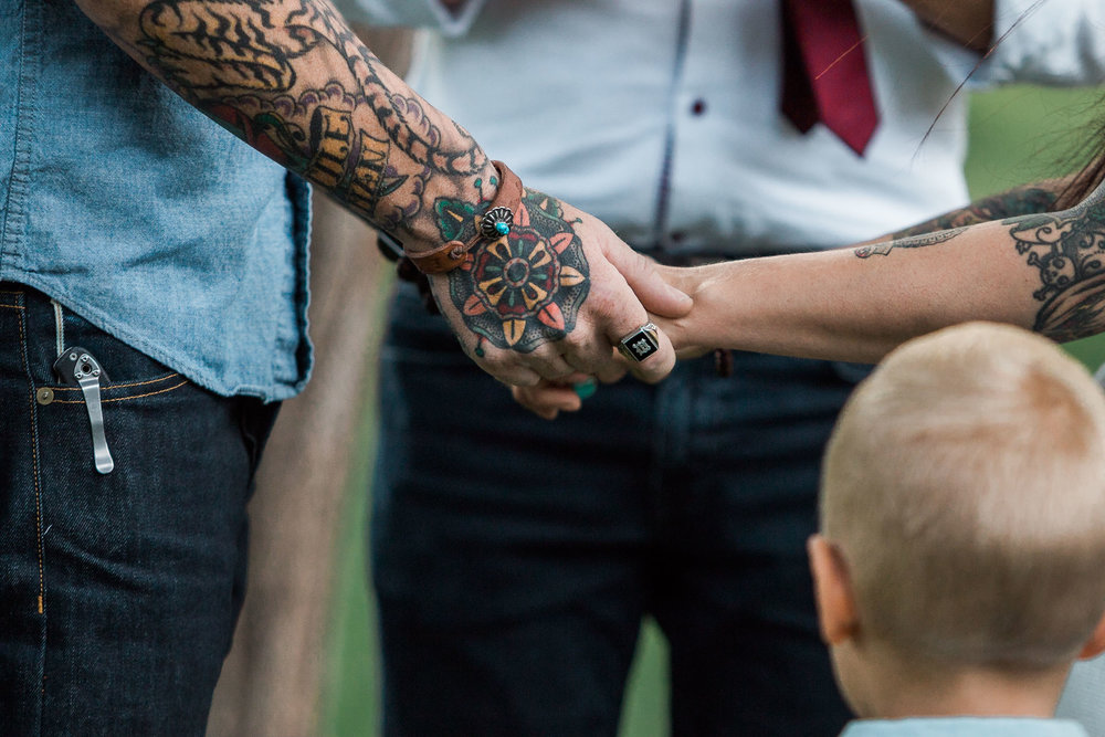Close up of tattooed hands holding during vow renewal ceremony in Springdale, Utah