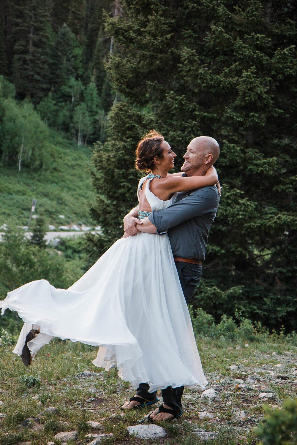 Husband spins wife in a flowy dress skirt during their adventure vow renewal in Jordan Pines, Utah