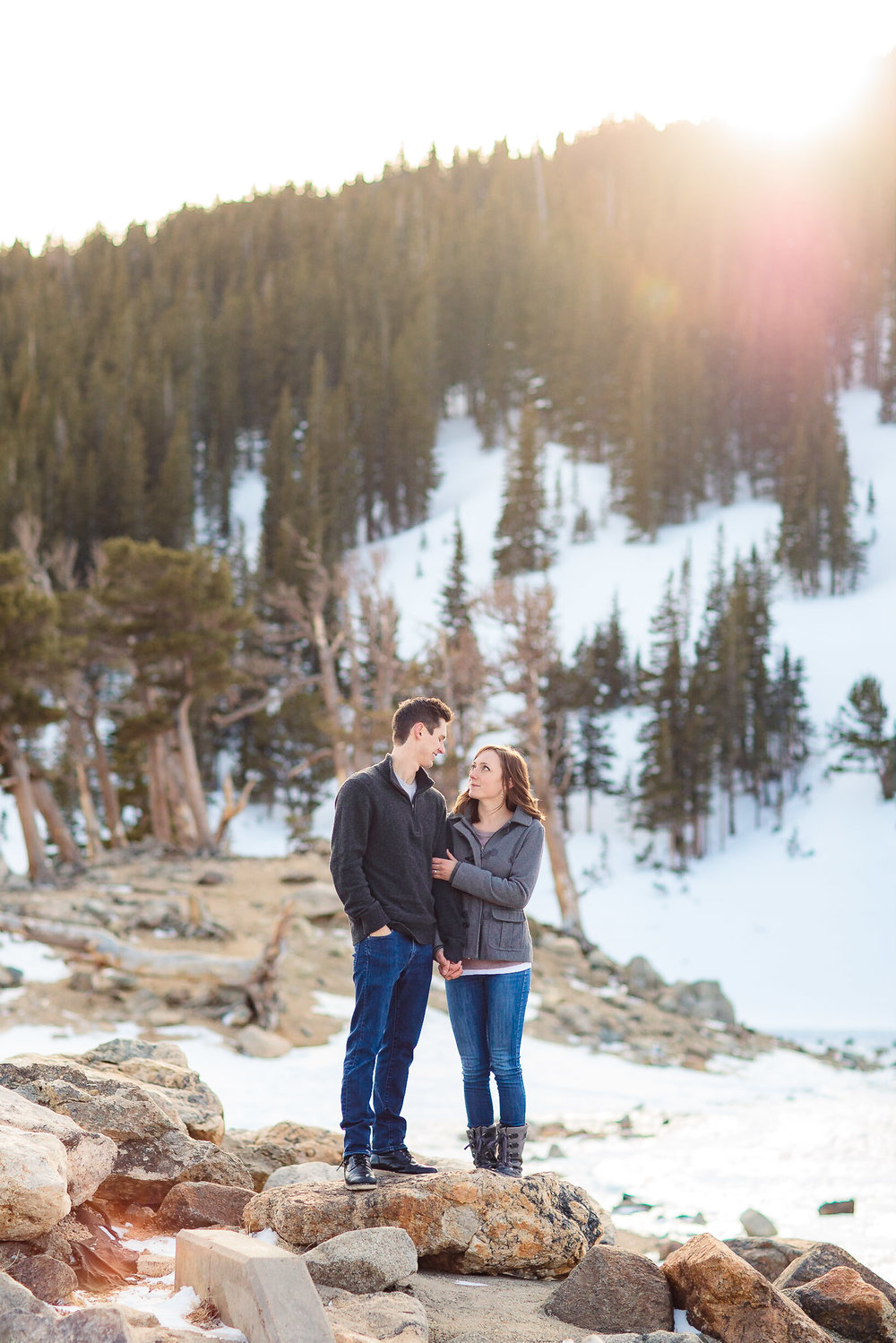 Couple look at each other while standing beside a snow covered lake for their adventure winter engagements at St. Mary's Glacier, Colorado