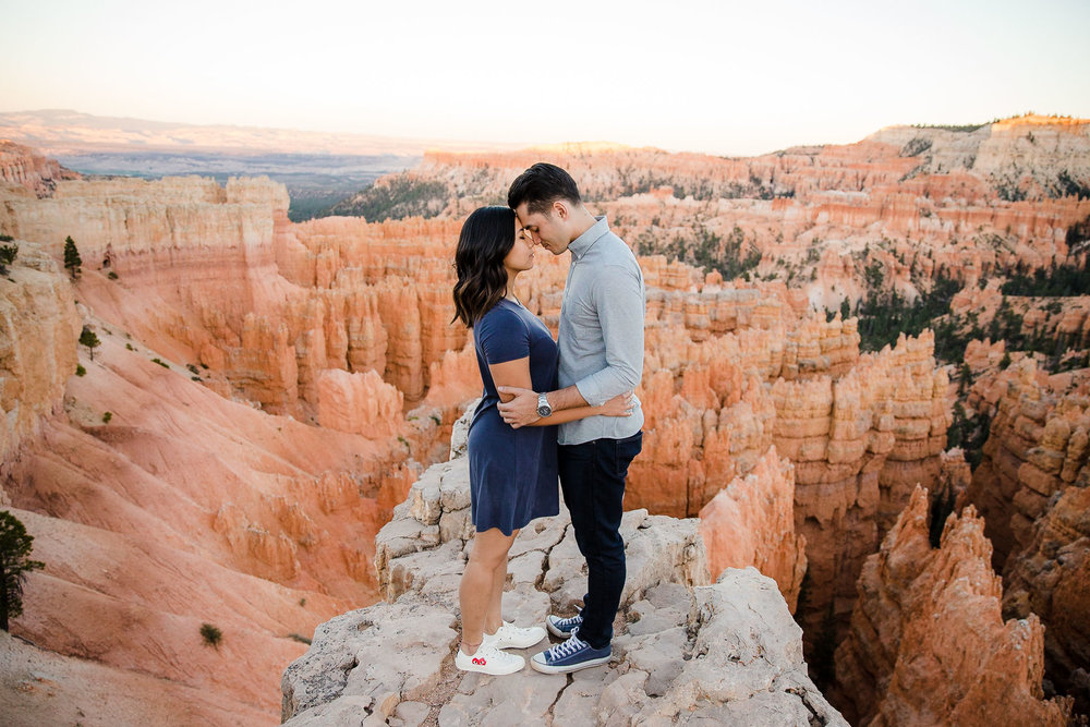 Couple stand together with Bryce Canyon hoodoos behind them for their adventure engagement session in Utah