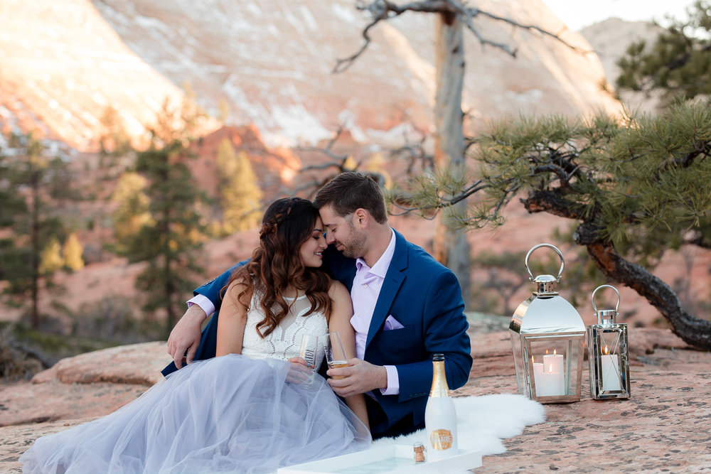 Couple snuggle on a blanket during their adventure engagement session in Zion National Park Utah