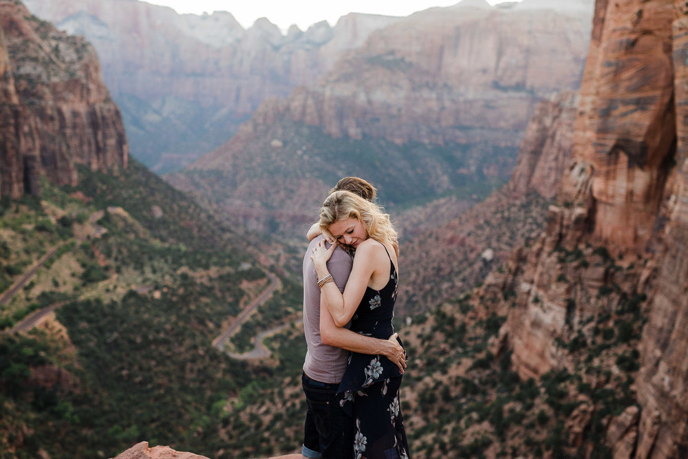 Couple hold each other close at Canyon Overlook viewpoint in Zion National Park