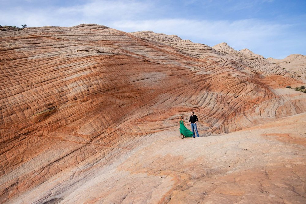 Couple hold hands in the epic swirling red rocks near St. George Utah for their adventure session