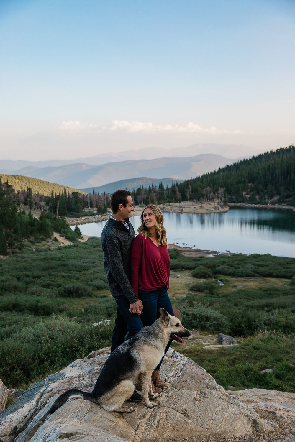 Couple stand with their dog in the Rocky Mountains for their adventure session in Colorado