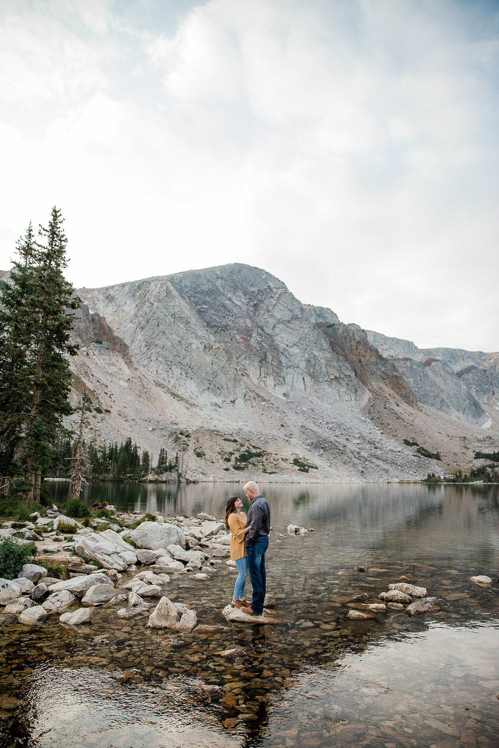 Couple stand on rock in a lake in the shadow of Medicine Bow Peak for their Wyoming Adventure Engagements