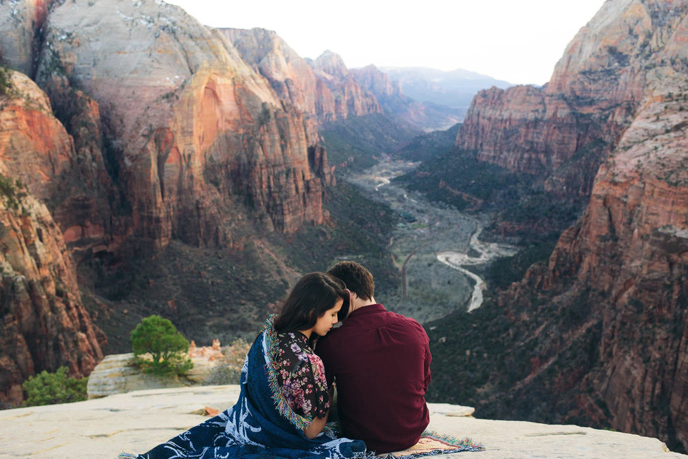 Couple snuggle wrapped in a blanket on Angel's Landing in Zion National Park for their adventure engagement session