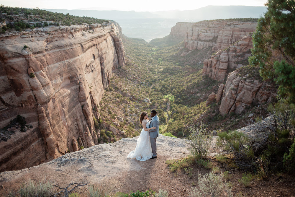 Interracial couple stand in front of epic view at the Colorado National Monument during their adventure wedding portraits
