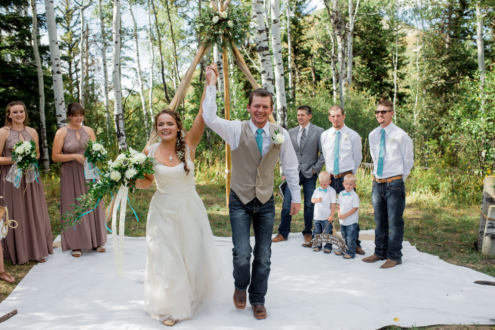 Bride and Groom cheer after ceremony during their adventure wedding in Colorado