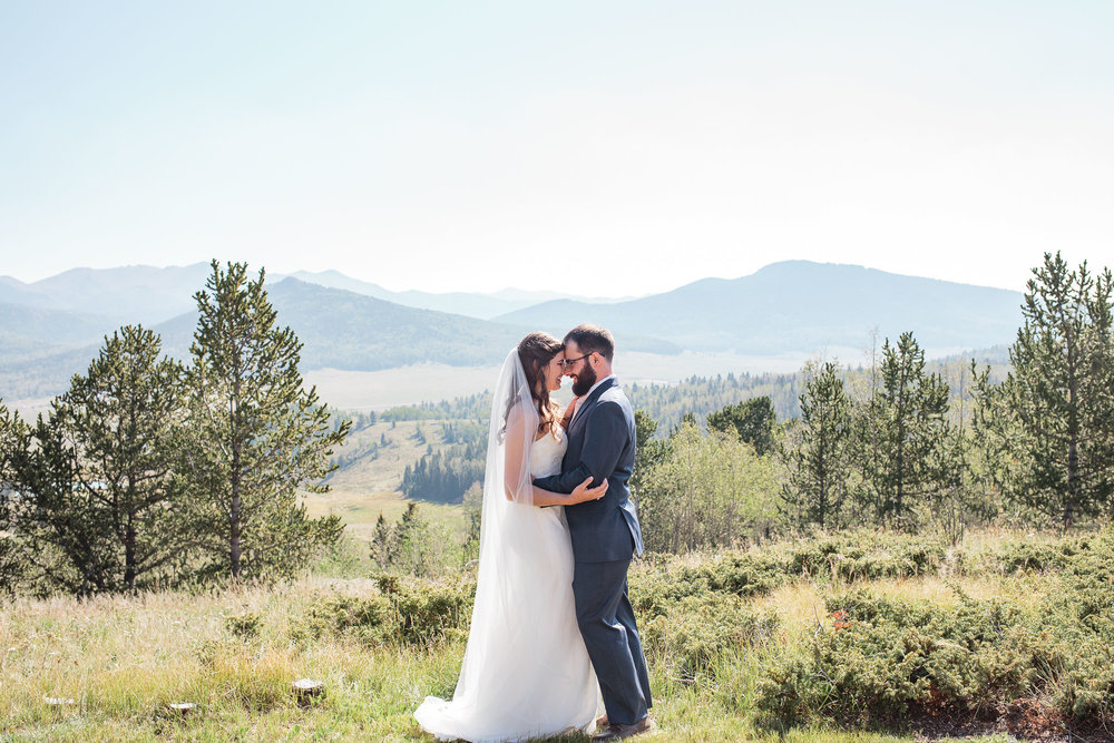 Wedding couple hug in front of view of Pikes Peak in Colorado