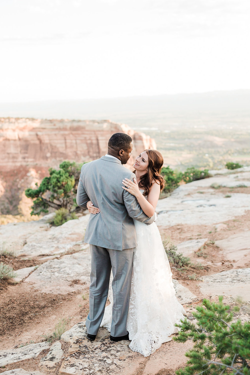 Interracial couple dance on the Colorado National Monument during their sunrise wedding portrait session
