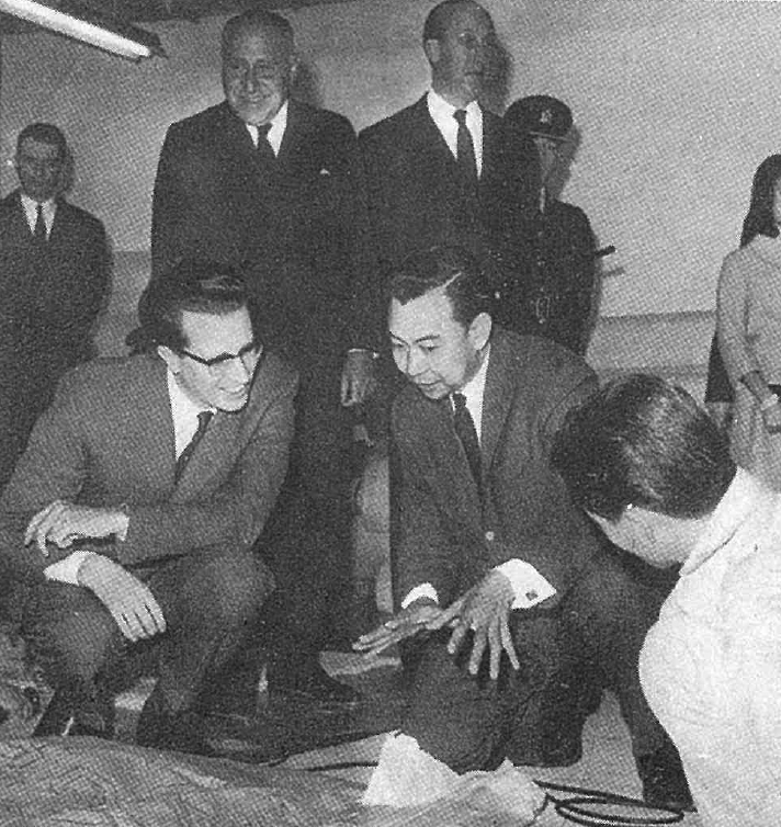 - Mr. Anthony Yeh explaining carpet production to His Majesty King Baudouin of Belgium, accompanied by Sir Lawrence Kadoorie (back)