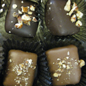 Miss Clara's Buttery toffee squares covered in milk or dark chocolate, topped with crushed pecans