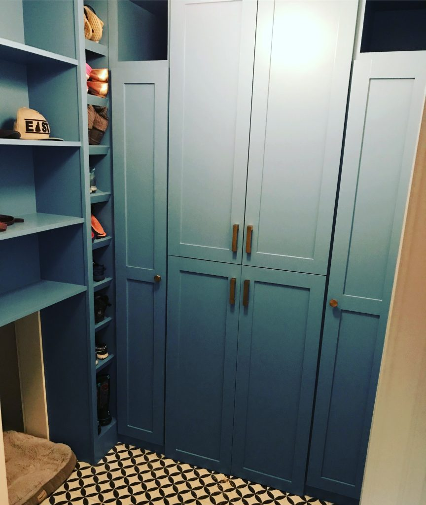 "Even the mudroom sports modern elements. The floor has black-and-white tiles whose pattern is similar to that in the kitchen backsplash. ""You see both patterns at the same time, and we didn't want them to compete,"" says Jerde. The vibrant blue cabinets have brass hardware, and a ceiling fixture brings out the different shades of blue."