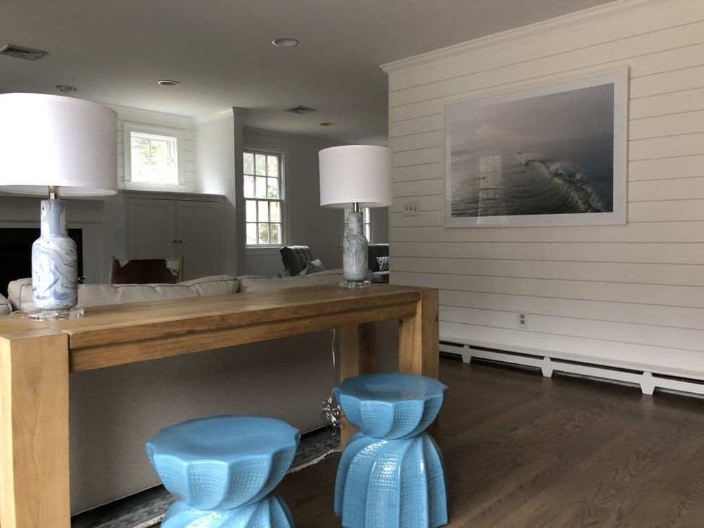 "In keeping with the color scheme, more muted blues and grays distinguish the family room. Striking blue ceramic stools from Shop Candelabra add a splash of color in the console area between the kitchen and the family room. ""We needed to keep that space open yet we wanted a design element there,"" says Jerde."