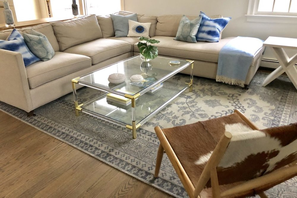 "For the family room, Jerde chose an oriental rug from Caitlin Wilson and paired it with a lucite-and-brass coffee table from Jayson Home. Throw pillows on the couch are by Susan Connor and Rebecca Atwood, both based in Brooklyn.  ""This was the first time I ever worked with a designer,"" says Sarah Hines. ""I thought it would be overwhelming, but Maggie made it fun and comfortable and really offered a greater perspective.""   —Marina Davalos"