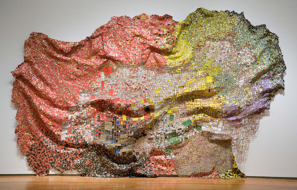 Artist El Anatsui creates gorgeous wall hanging sculptures with recycled liquor bottle tops.