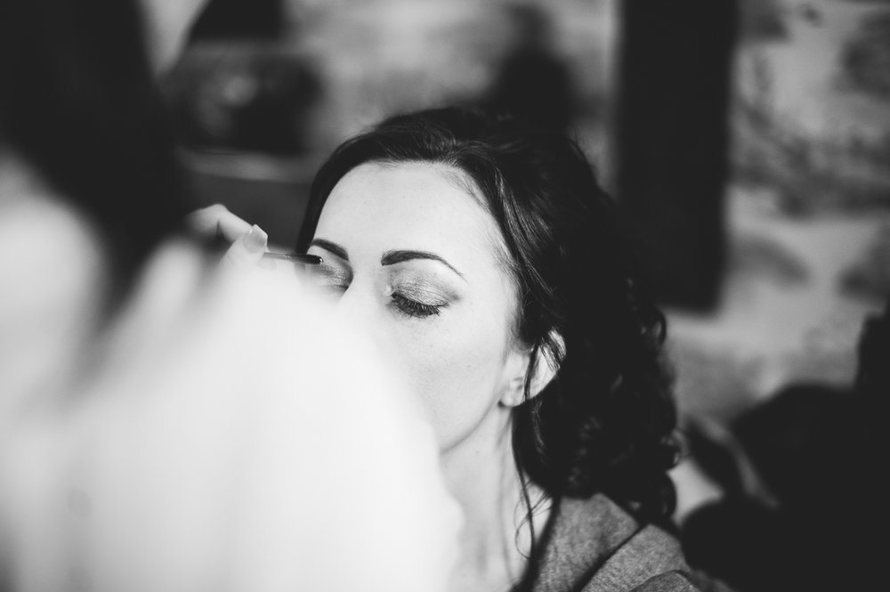 Bride having her make up done on the morning of her wedding. Black and white photo.