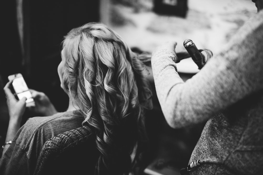 Bridesmaid having her hair curled at the bridal preps. Black and white photography