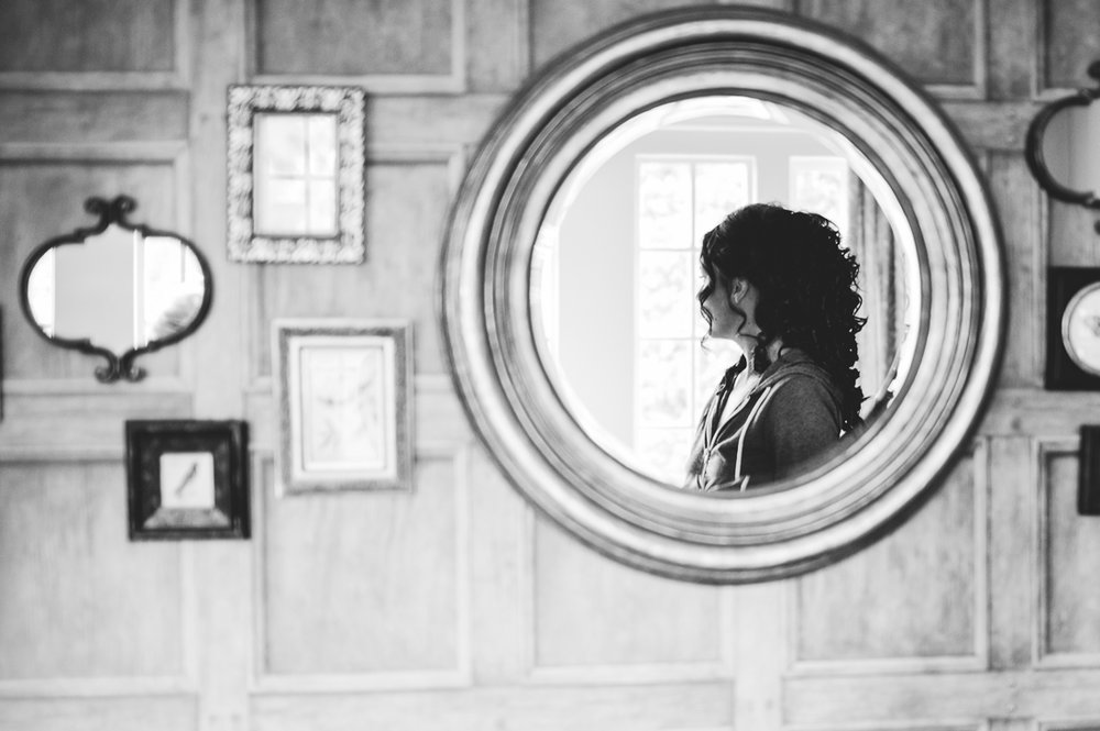 Reflection of the bride in a mirror at Eaves Hall wedding venue. Lancashire wedding photography