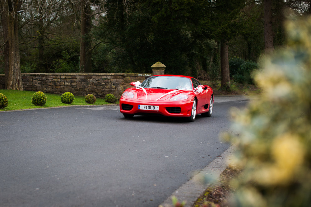 Red Ferrari coming up the drive at Eaves Hall
