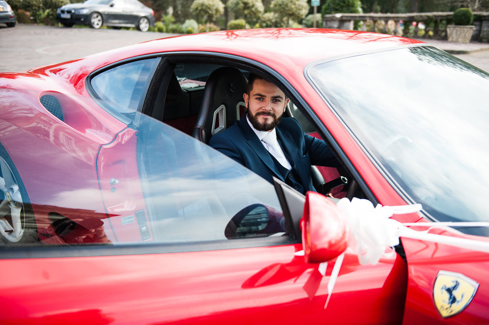 Groom arriving at Eaves Hall in a red Ferrari