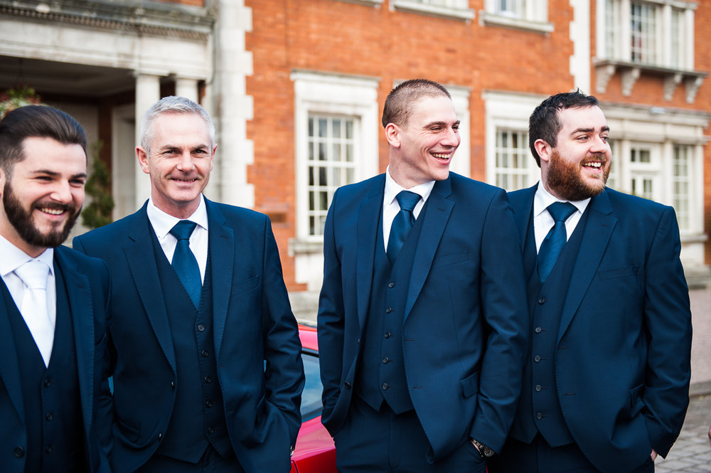 Natural photograph of the groomsmen stood together outside at Eaves Hall, Cliteroe