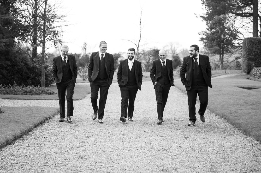 Natural black and white photo of the groomsmen walking together outside at Eaves Hall
