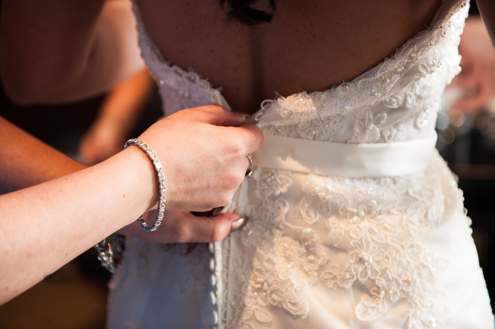 Close up of brides dress being fastened