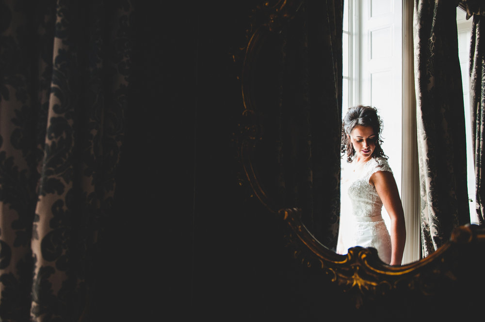 Documentary photography of the bride as she stand by the window.