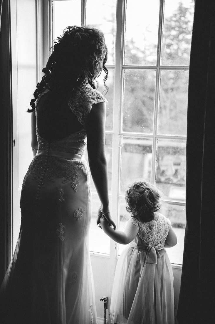 Bride and her daughter looking out of the window at Eaves Hall in Clitheroe. Lancashire wedding photography