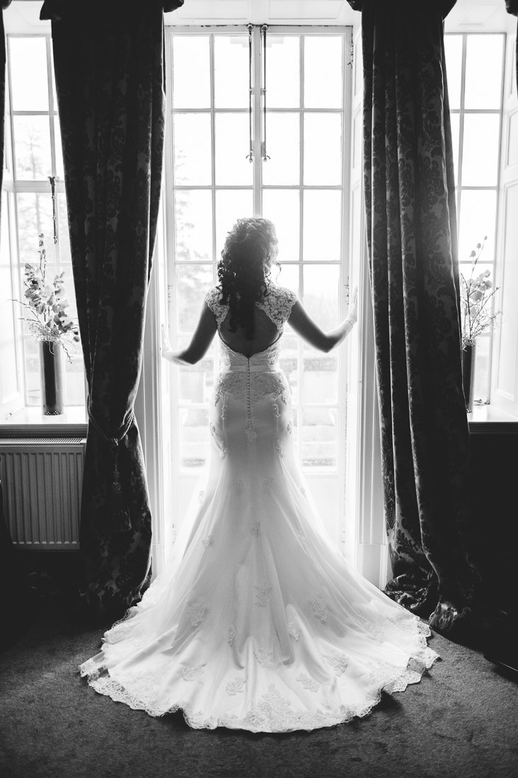 Full length shot of the brides dress as she stands in front of the window at Eaves Hall