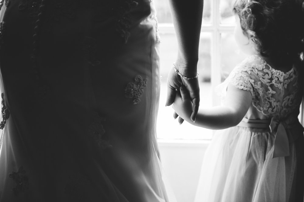 close up shot of bride and daughter holding hands. black and white wedding photography