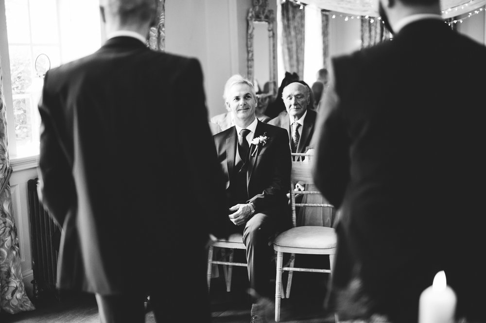 Documentary photography of Grooms father laughing with the groom before bride arrives