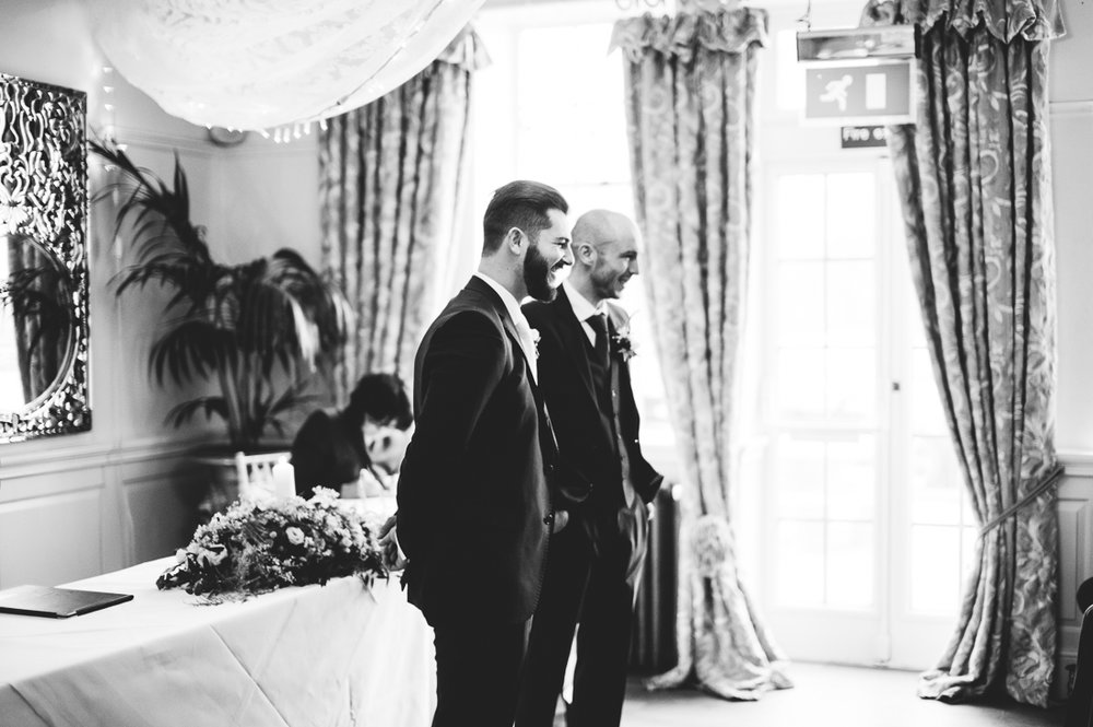 Groom and Best man wait in the isle for the bride to arrive at Eaves Hall wedding