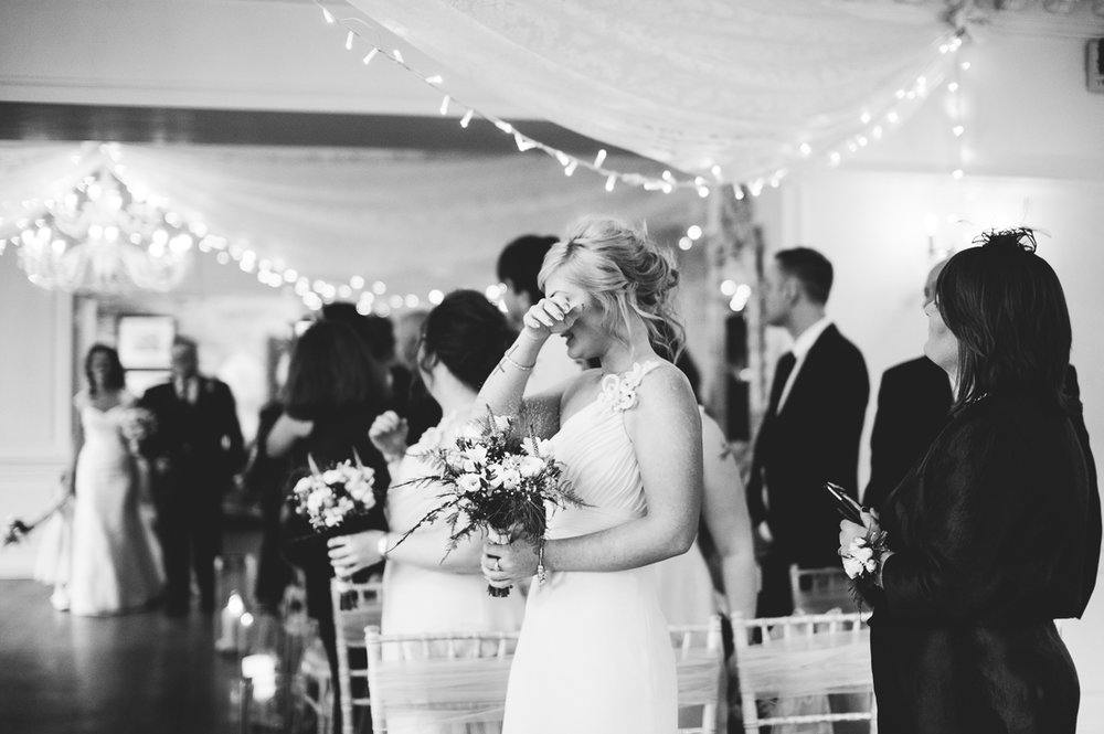 Documentary photography of the bridesmaid crying as the bride enters the room
