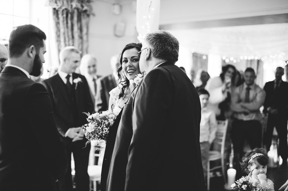 Documentary shot of the father of the bride kissing bride before giving her away