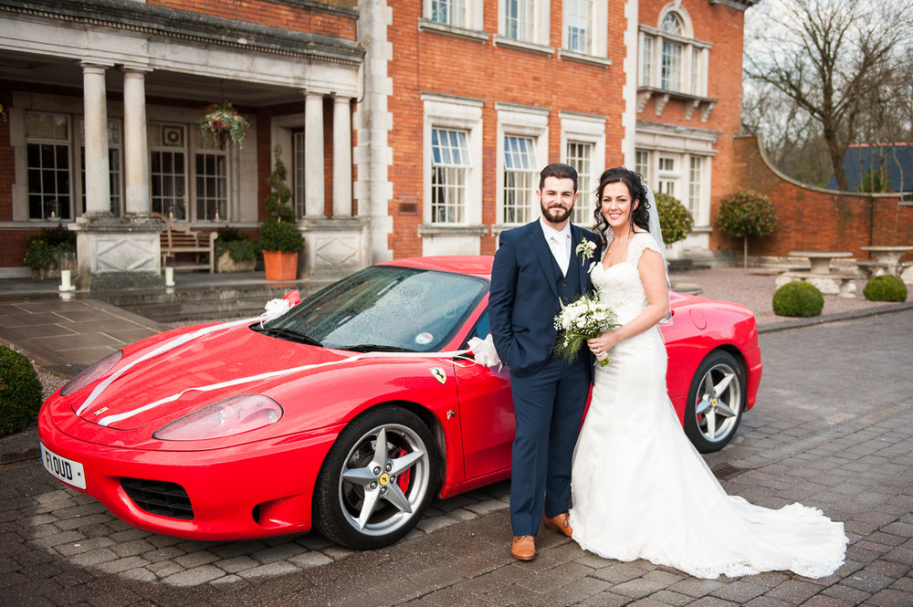 Bride and groom outside of Eaves Hall next to red Ferrari