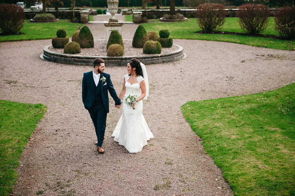 Bride and groom walking together through the grounds of Eaves Hall. Documentary wedding photography