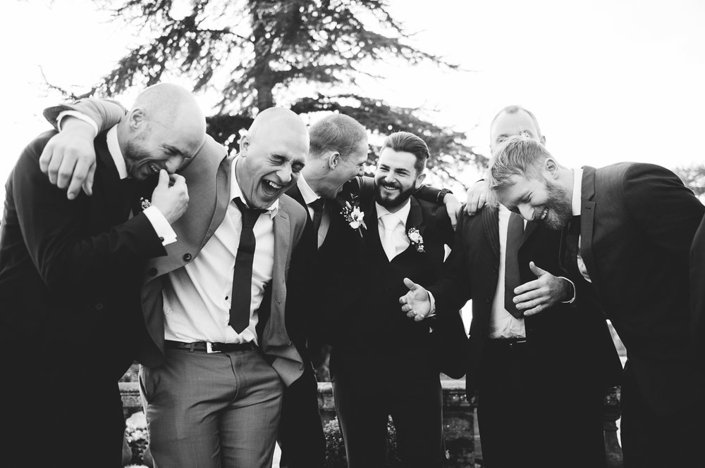 Natural shot of the groomsmen laughing
