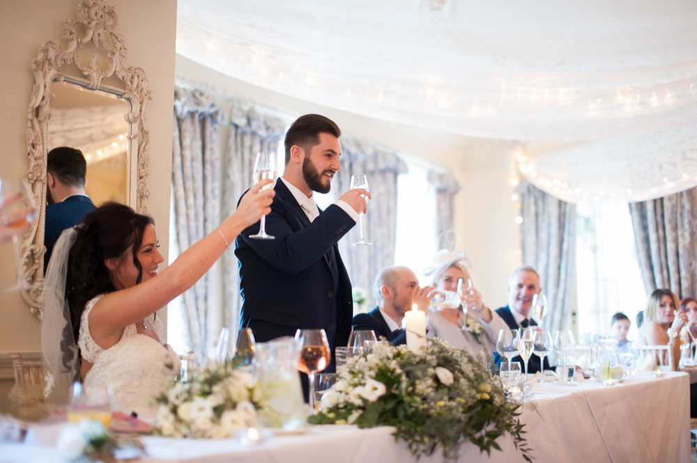 Bridal party raising a toast during the speeches at Eaves Hall