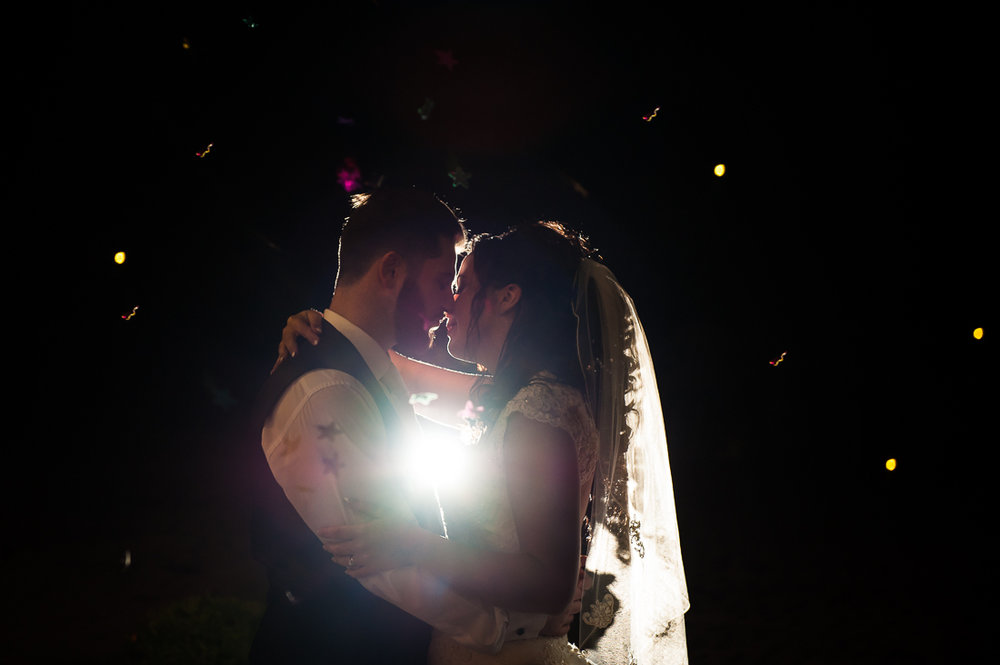 Night time confetti shot with bride and groom
