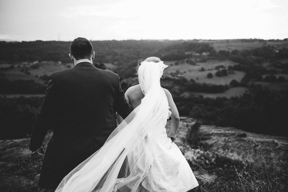 Documentary shot of couple walking on the hillside at their Yorkshire Wedding.