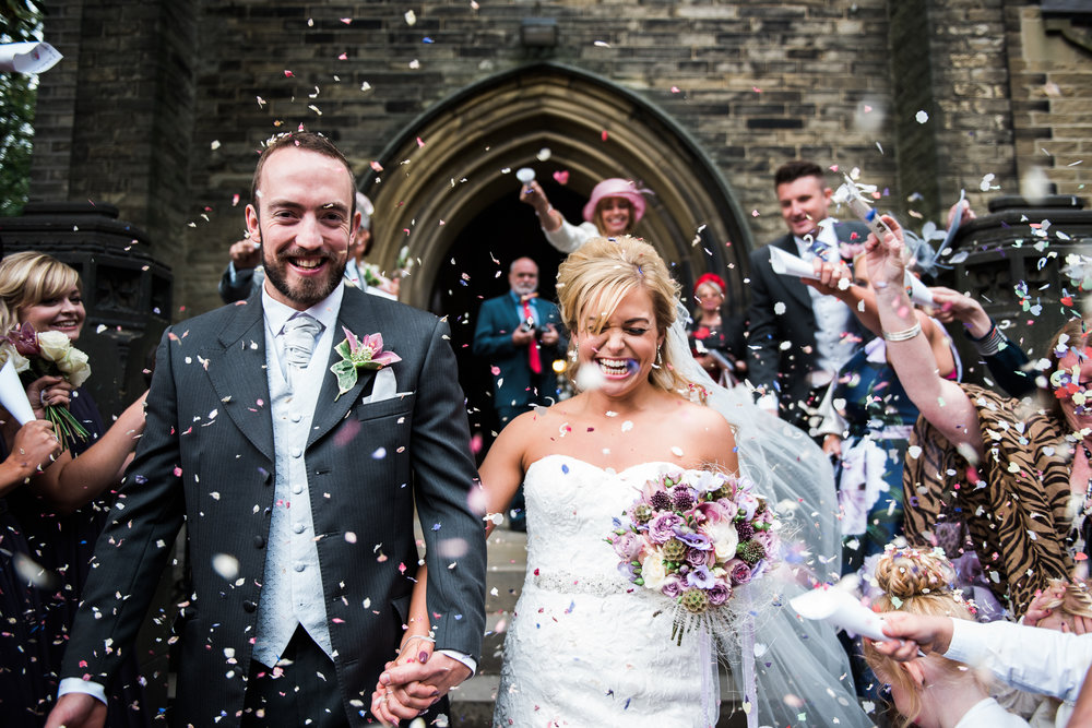 Confetti shot with bride and groom as they leave church. Yorkshire wedding photography.