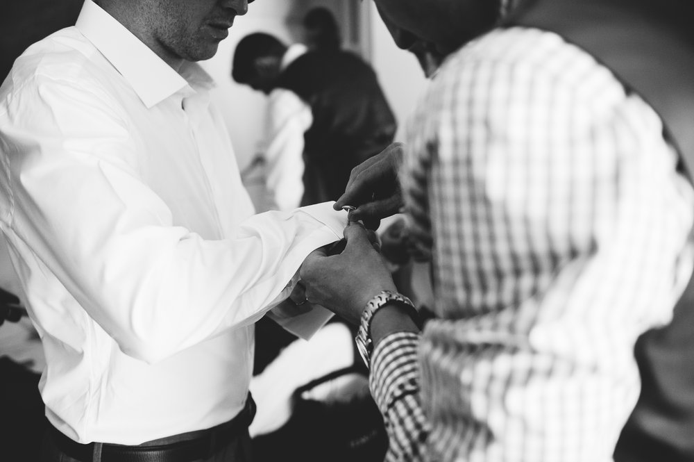 groom doing cufflink up. Natural documentary wedding photography