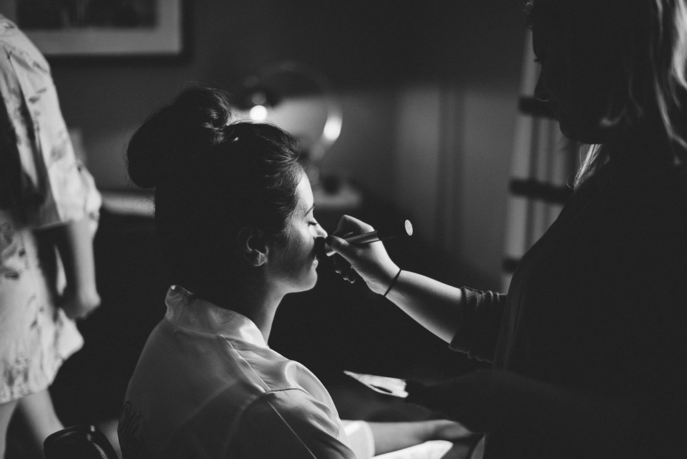 natural black and white shot of the bride having her makeup done the morning of her wedding at Northcote Manor, Lancashire.